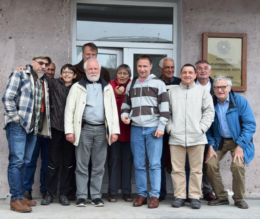 Neun Männer, eine Frau und ein Junge stehen vor dem Eingang eines Gebäudes