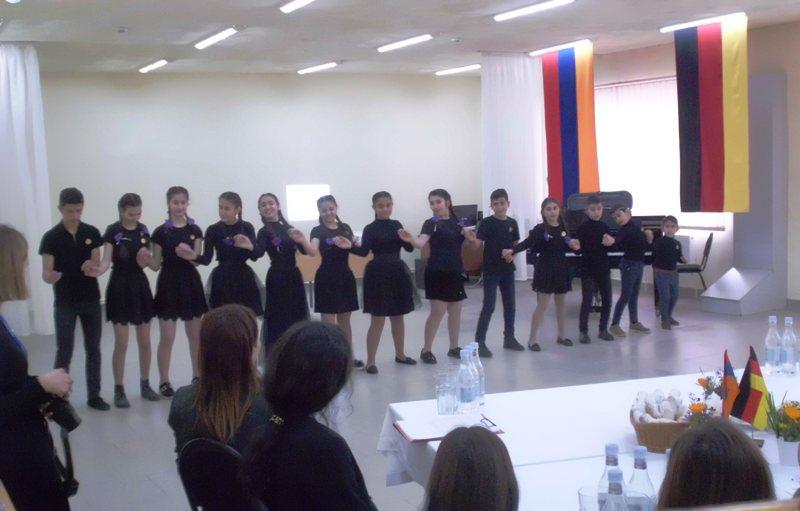 Kinder in schwarzer Kleidung stehen in einer Reihe zum Tanz; im Hintergrund hängen die deutsche und die armenische Fahne an der Wand