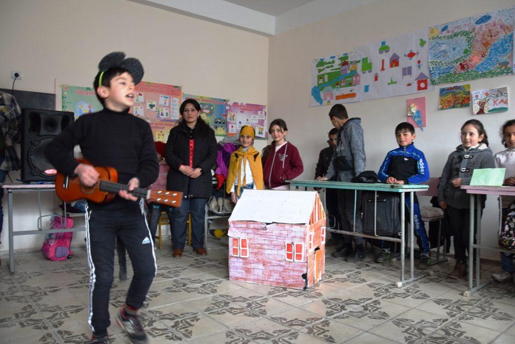 Ein Junge mit einer kleinen Gitarre umkreist singend ein kleines Haus; im Hintergrund stehen und sitzen mehrere Kinder und Erwachsene; an den Wänden dahinter hängen gemalte Bilder