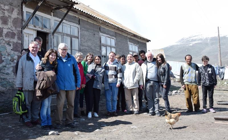 Eine Gruppe Menschen steht vor einem niedrigen langen Gebäude