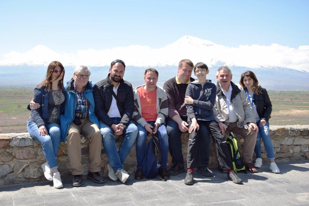 Fünf Männer, zwei Frauen und ein Junge sitzen auf einer Mauer; im Hintergrund Berge und Wolken