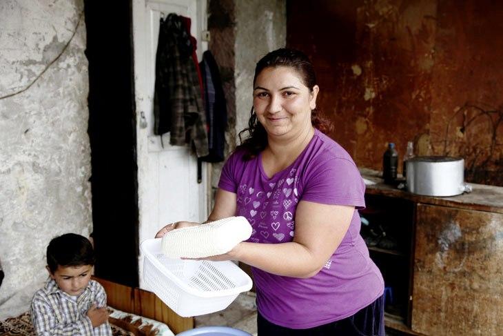 Frau zeigt den selbst hergestellten Käse