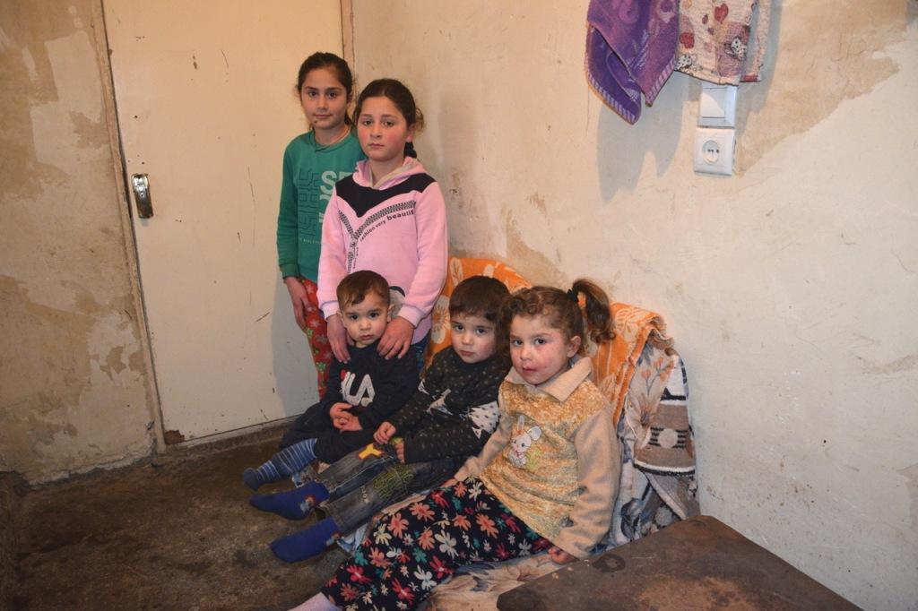 Fünf Kinder; drei sitzen, zwei stehen