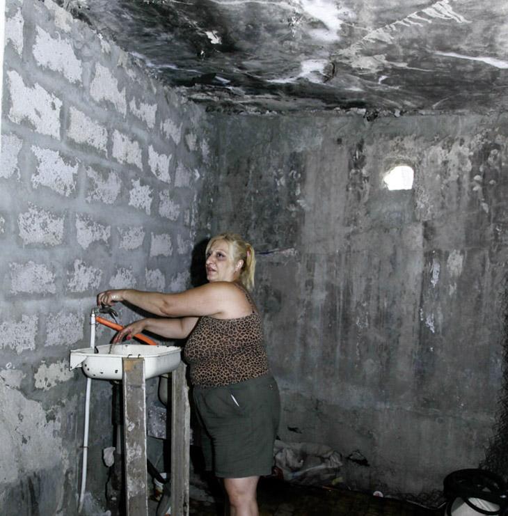 Eine Frau steht in einem Raum mit kahlen grauen Wänden an einem Waschbecken