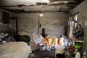 Mit Möbeln und anderen Dingen überfüllte Wohnung; die Wände und die Decke sind kahl und offenbar schimmelig; Teile der Decke lösen sich