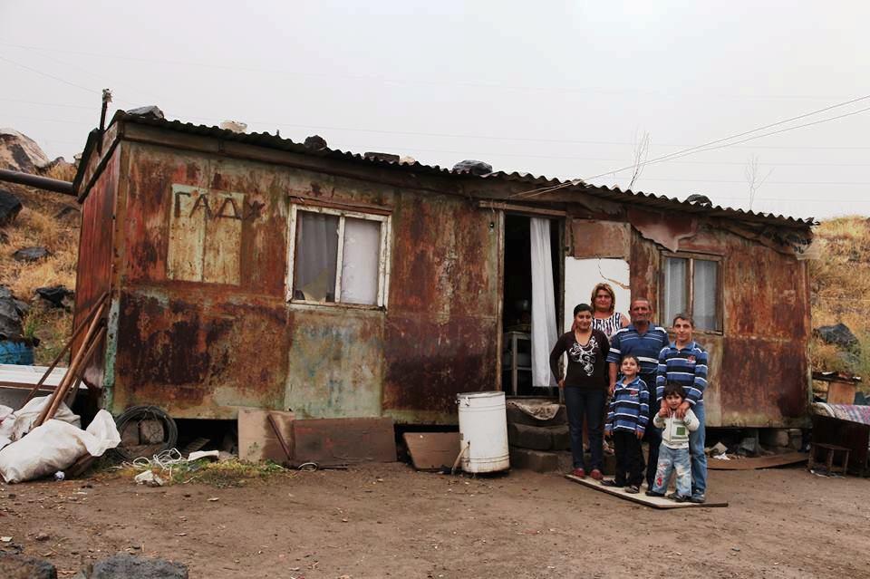 Sechs Personen - Erwachsene und Kinder - stehen vor einer Hütte aus verrostetem Blech