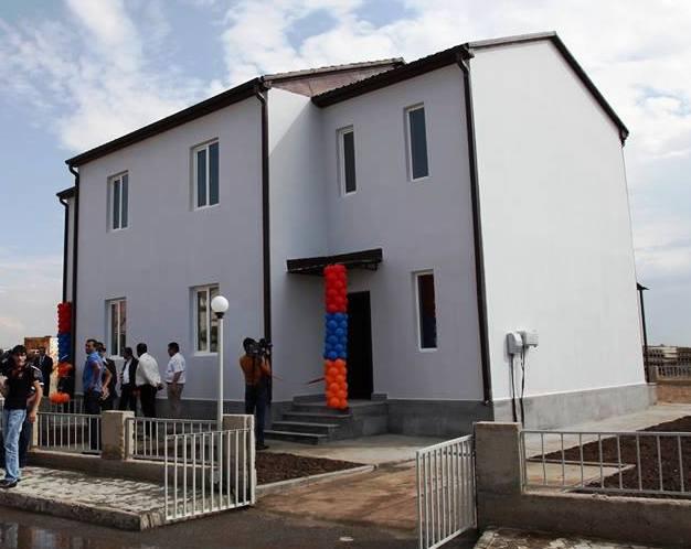 Mehrere Personen stehen vor einem zweistöckigen weißen Haus mit Satteldach; am Eingang befinden sich Luftballons in rot, blau und orange