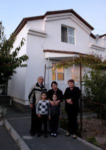 Fünf Personen stehen vor einem zweistöckigen Haus mit Garten