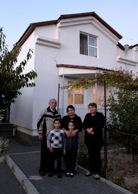 Drei Erwachsene und zwei Kinder stehen vor einem zweistöckigen weißen Haus