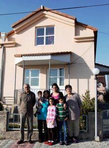 Sieben Personen, darunter ein Kind, das auf dem Arm getragen wird, vor einem zweistöckigen Haus