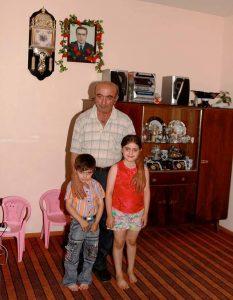 Großvater mit zwei Enkelkindern, einem Jungen und einem Mädchen; im Hintergrund das blumengeschmückte Porträtfoto eines Mannes