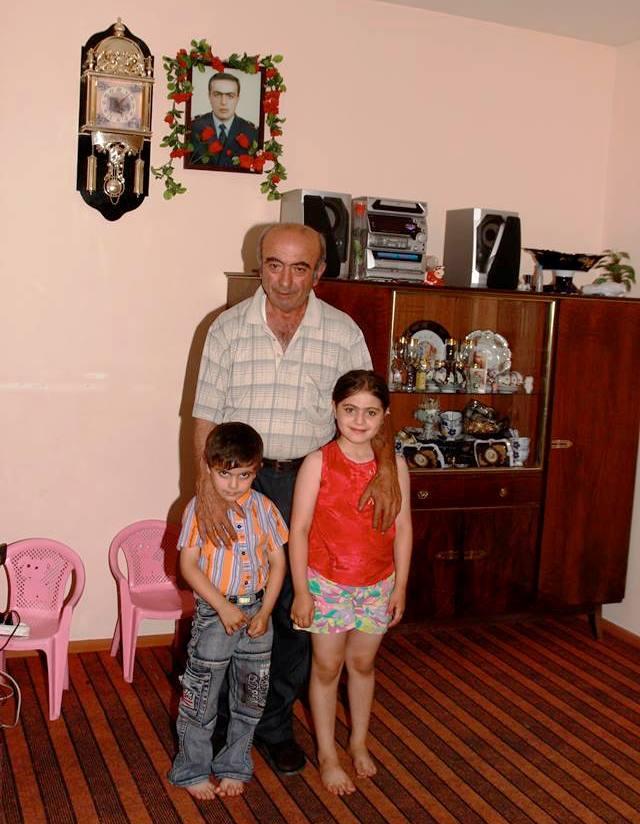 Ein älterer Mann und zwei Kinder stehen vor dem blumengeschmückten Porträt eines jungen Mannes