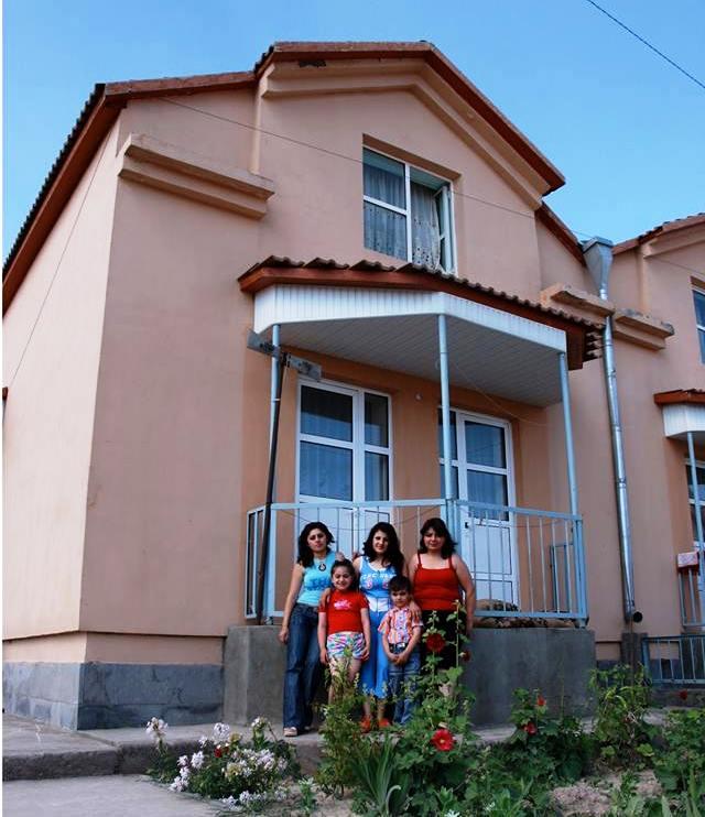 Drei Frauen und zwei Kinder stehen vor einem rosafarbenen zweistöckigen Haus