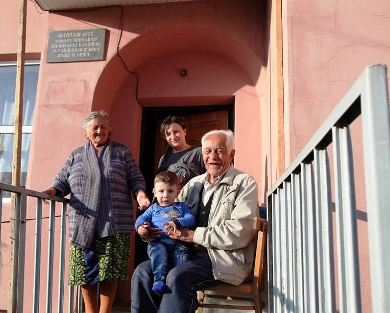 Ein älterer Mann sitzt mit einem Kind auf dem Schoß vor einem Hauseingang, hinter ihm stehen eine ältere und eine jüngere Frau