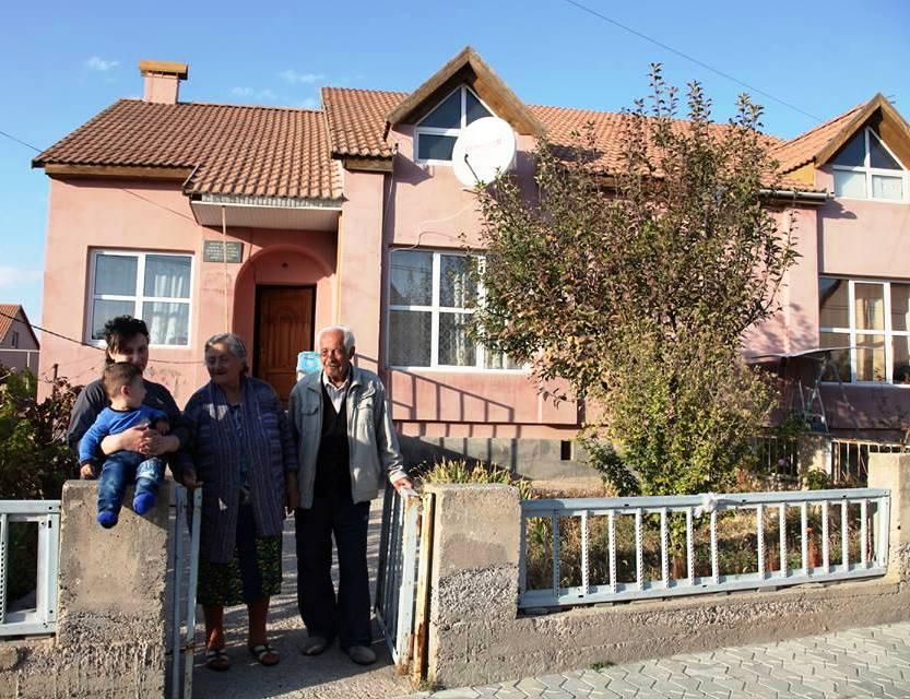 Drei Erwachsene stehen vor einem rosafarbenen zweistöckigen Haus, ein kleiner Junge sitzt auf einem Mauerpfosten
