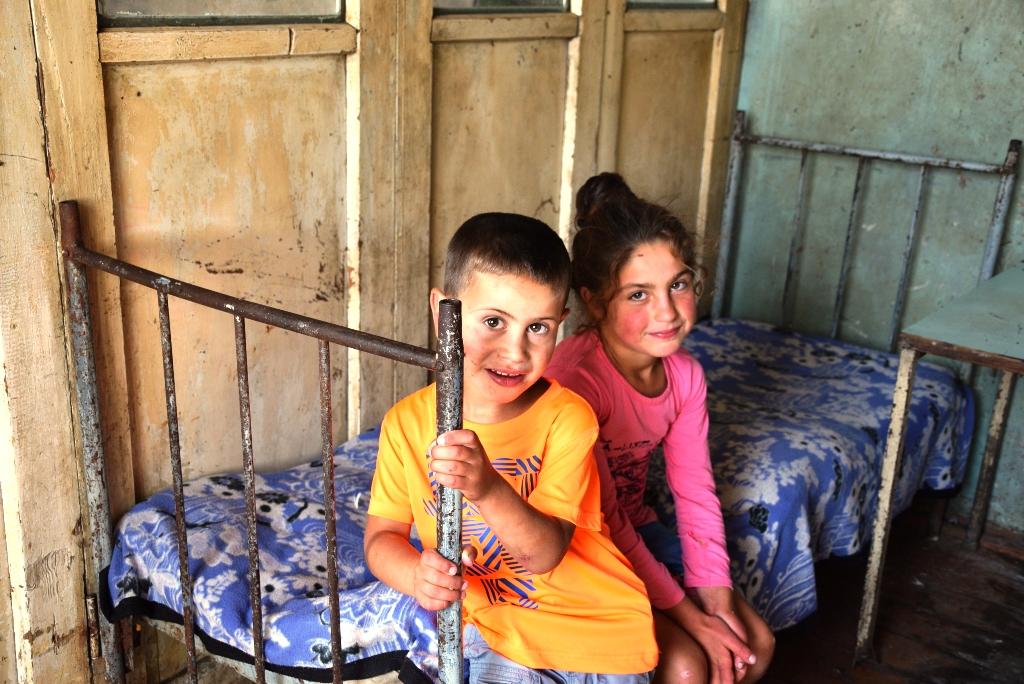 Ein junge und ein Mädchen sitzen auf einem Bett