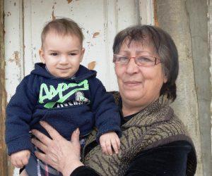 Ältere Frau hält kleines Kind auf dem Arm