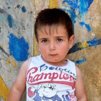Dunkelhaariger Junge in weißem ärmellosen Shirt mit Aufdruck vor einer bunten Wand