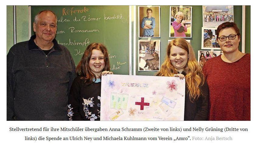 Ein Mann und eine Frau mit zwei Mädchen, die ein Bild hochhalten, das aufgemalte Geldscheine zeigt