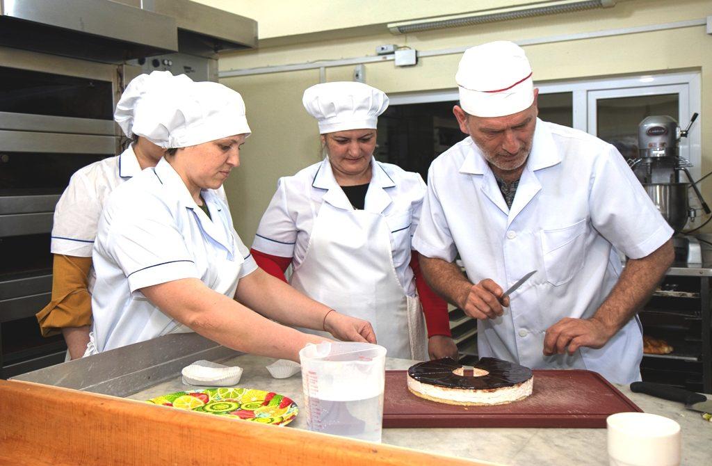 Bäcker-Ausbildung im Berufsausbildungszentrum BAZ - Ein Ausbilder und drei weibliche Auszubildende stehen vor einem Kuchen; der Ausbilder hält ein Messer