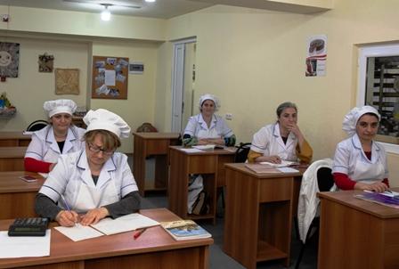 Bäcker- und Konditorenausbildung - Fünf Frauen in weißer Bäckerkleidung sitzen jeweils an einem Einzelpult und notieren etwas auf vor ihnen liegenden Zetteln