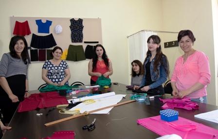 Näherinnenausbildung - Sechs Frauen stehen um einen Tisch, auf dem Stoff und verschiedene Utensilien zum Zuschneiden liegen