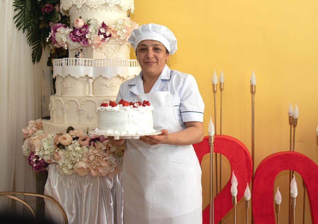 Eine Frau in Bäckerkleidung hält eine Sahnetorte mit Erdbeeren in den Händen; neben ihr befindet sich eine Dekoration in Form einer überdimensionalen mehrstöckigen Torte