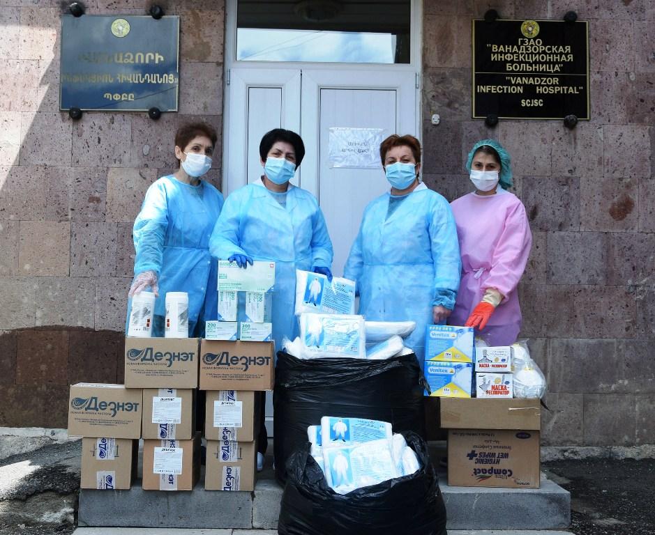 Vier Frauen in Schutzkleidung stehen hinter einigen aufgestapelten Paketen, die Schutzkleidung und Desinfektionsmittel erhalten
