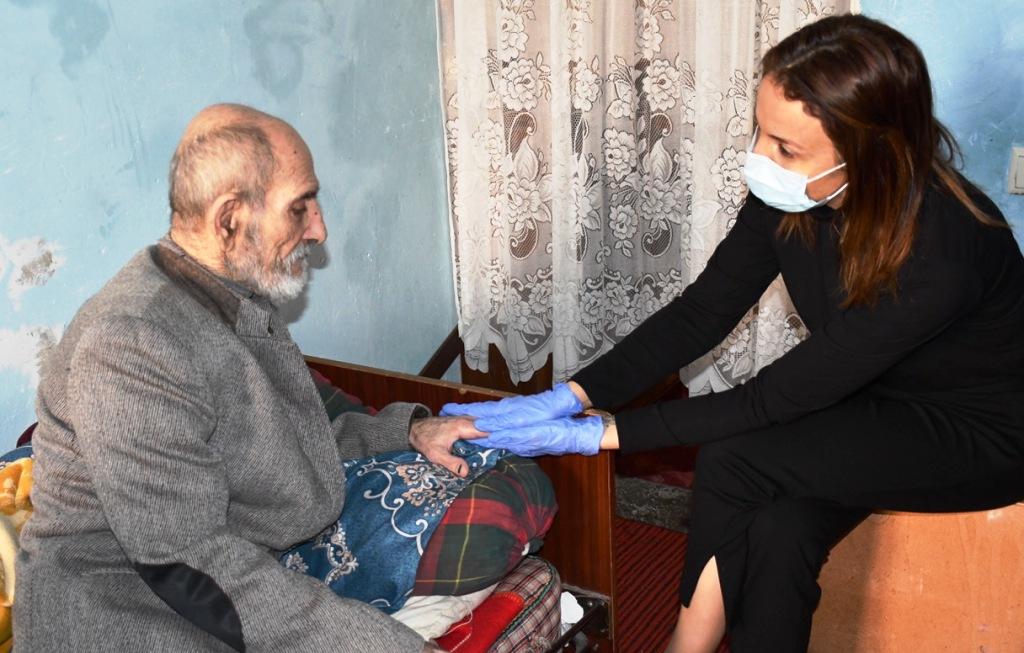 Eine jüngere Frau mit Mund-Nasen-Schutz und Handschuhen hält die Hand eines älteren Mannes