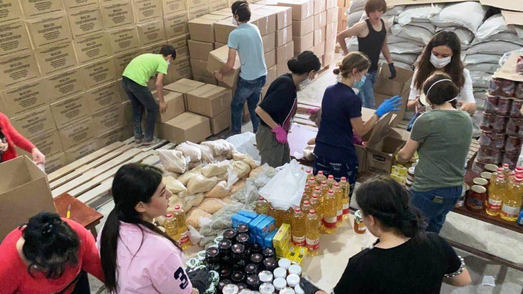 Eine Gruppe Menschen packt Lebensmittelpakete