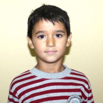 Dunkelhaariger Junge in rot-weiß gestreiftem Shirt schaut ernst in die Kamera