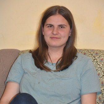 Eine Jugendliche mit braunem Haar sitzt auf einem Sofa