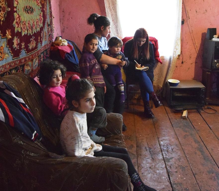 Frau mit vier Kindern sitzt auf einem Sofa, Frau sitzt auf einem Stuhl und schreibt