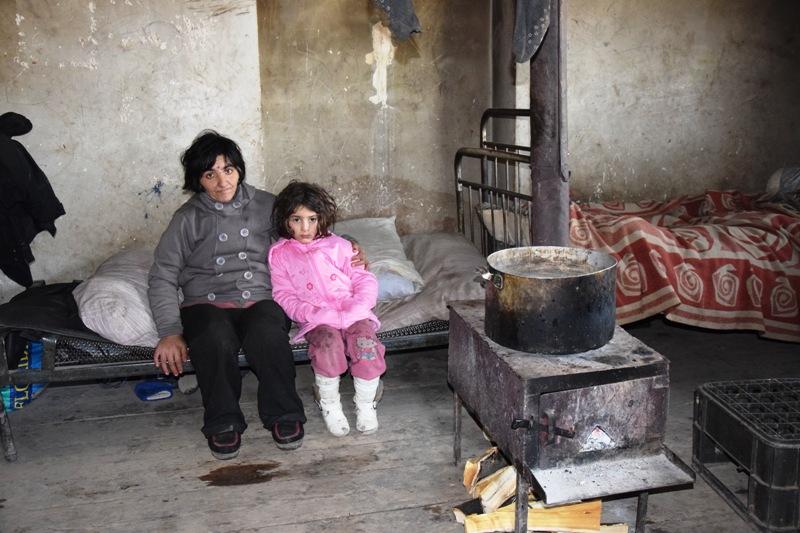 Frau und Mädchen sitzen in einem ärmlichen Zuhause