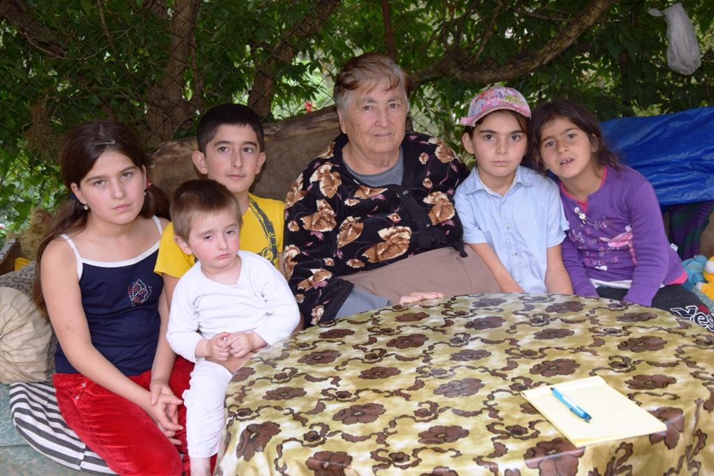 Ältere Frau und fünf Kinder sitzen am Tisch