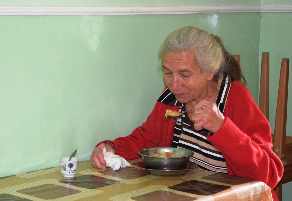 Alte Frau sitzt am Tisch und isst