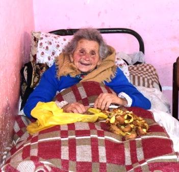 Alte Frau im Bett mit Kartoffelschalen auf der Decke