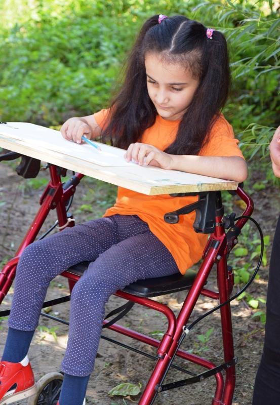 Mädchen sitzt auf einem Rollator und malt