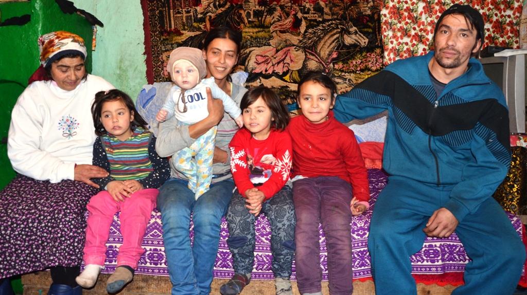 Zwei Frauen, ein Mann, vier Kinder sitzen auf einem Sofa