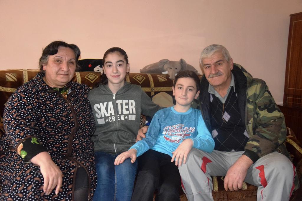 Vier Personen sitzen auf einem Sofa - von links: ältere Frau, Mädchen, Junge, älterer Mann