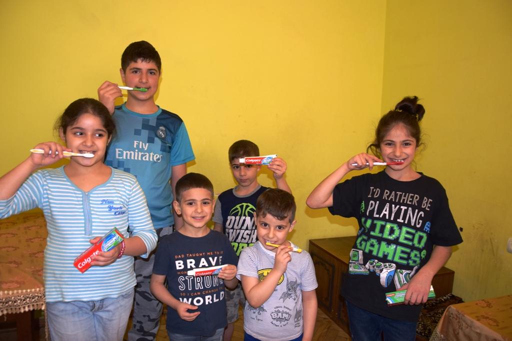 Sechs Kinder unterschiedlichen Alters halten Zahnpasta und imitieren mit Zahnbürsten das Zähneputzen