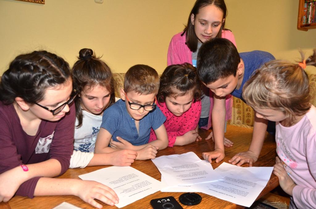 Sieben Kinder beugen sich über Zettel auf einem Tisch