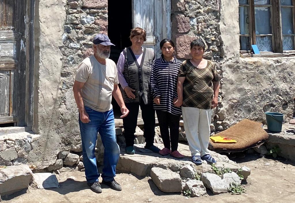 Drei Frauen und ein Mann stehen vor der Tür eines Hauses, das aus groben Steinen gebaut ist