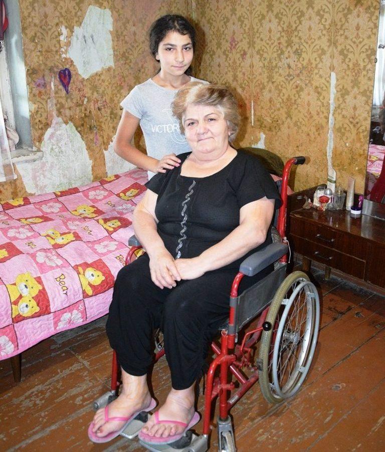 Eine Frau sitzt im Rollstuhl, hinter ihr steht ein Mädchen
