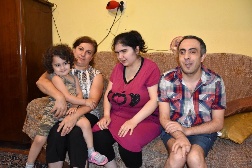 Ein Kind, zwei Frauen und ein Mann sitzen auf einem Sofa