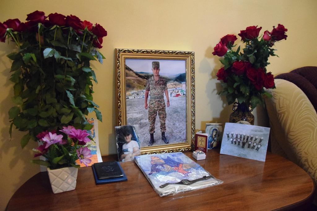 Foto von einem jungen Soldaten, umgeben von Blumen und anderen Fotos