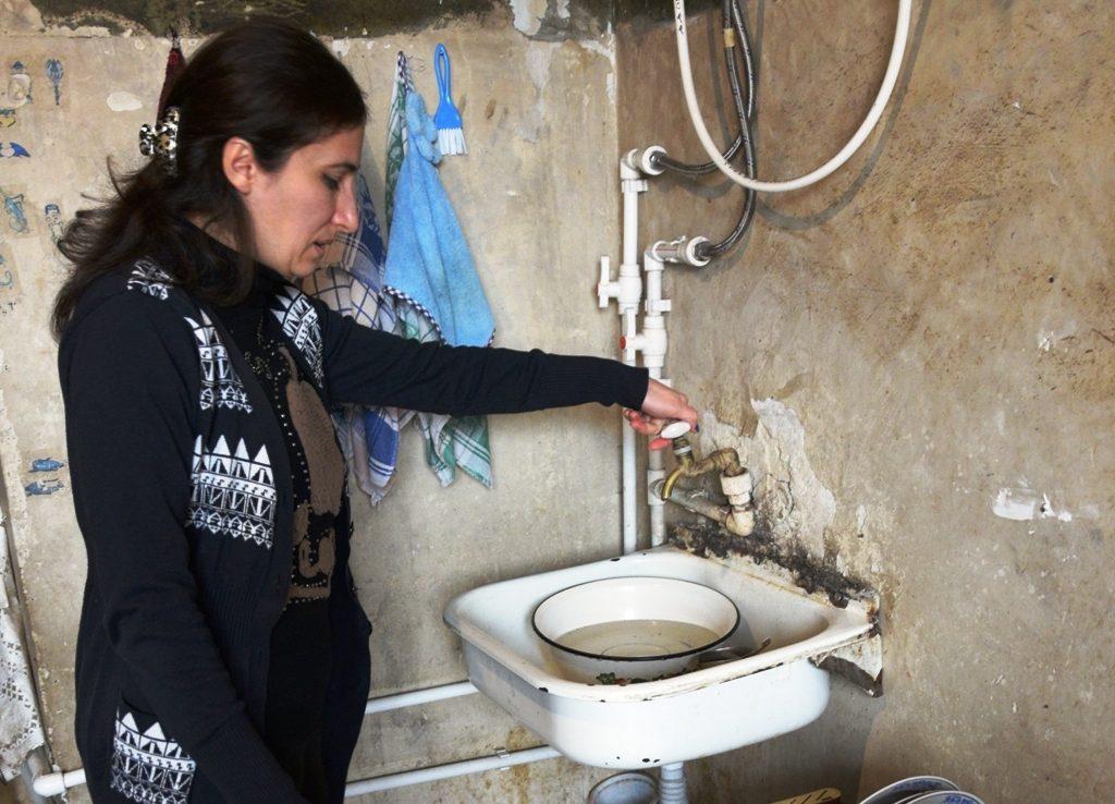Eine Frau steht in einem maroden Zimmer an einem Waschbecken