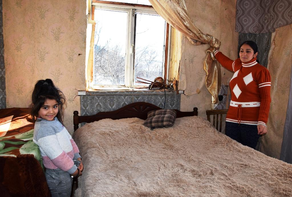 Frau steht am Fenster; die Scheiben wurden durch Folie ersetzt