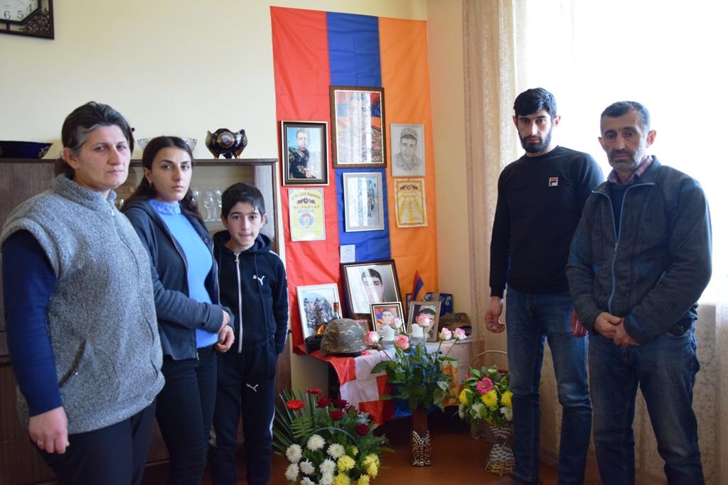 Zwei Frauen, zwei Männer und ein Junge stehen neben einem Gedenktisch für einen gefallenen Soldaten