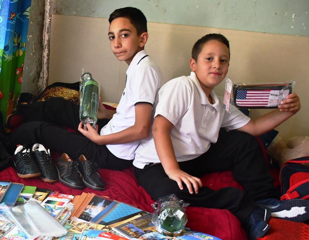 Bildung ist wichtig - zwei Jungen zeigen das Schulmaterial, das sie bekommen haben